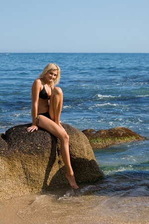Beautiful girl is sitting on a rock by the sea photo