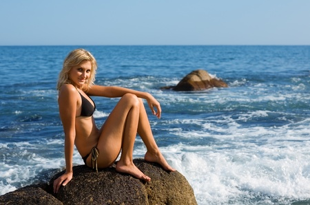Beautiful girl is sitting on a rock by the sea. photo