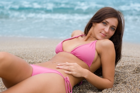 Beautiful girl lying on a sandy beach near the sea. photo