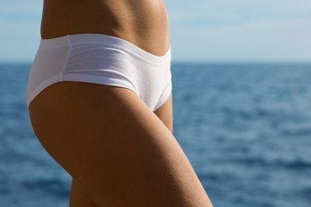 Body beautiful young woman in white pants. Sea.  photo