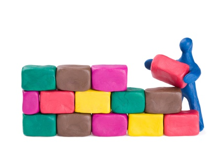 A plasticine little bricklayer building a brick wall.