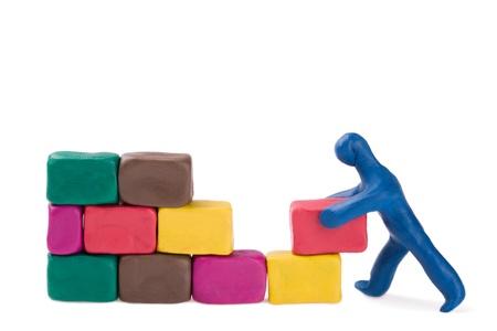 A plasticine little bricklayer building a brick wall.  photo