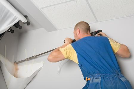fettler: Hombre simulacros pared perforadora de instalaci�n. Trabajar sobre la instalaci�n de un nuevo acondicionador de aire. Foto de archivo