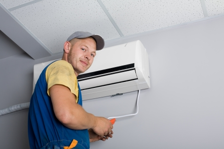 Young setup man installs the new air conditioner in the office. Stock Photo - 10298841