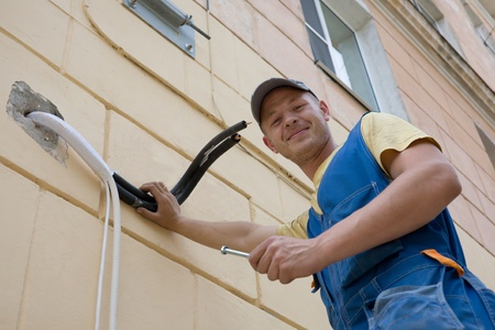 residential structures: Young setup man paves the technological pipelines for a new air conditioner.