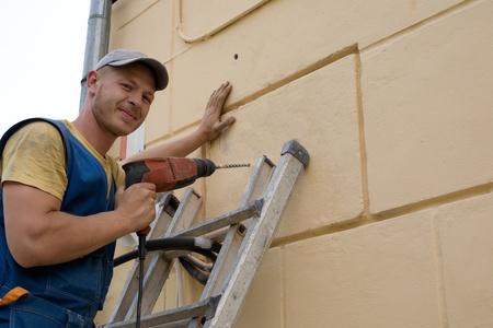 performs: L'uomo svolge un lavoro di impostazione su come installare un condizionatore d'aria nuova. Archivio Fotografico