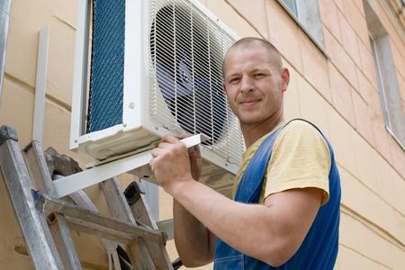 fettler: J�venes de instalaci�n hombre instala el nuevo aire acondicionado para oficina. Foto de archivo