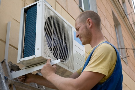 cold air: Young setup man installs the new air conditioner for office.