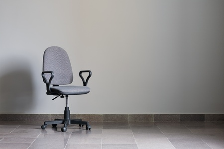 Office chair against a gray wall with sunlight. Stock Photo - 10306817
