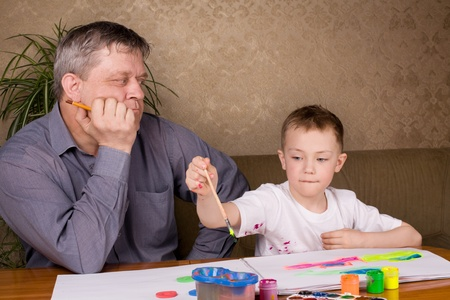 His grandfather teaches his grandson drawing paint. Stock Photo - 10306820