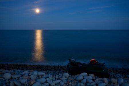 Full moon with reflection on sea. Marine rocky shore of a large pebble. On the shore of an inflatable boat.