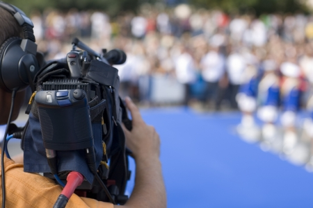 filming: Operator television camera during a public event space.