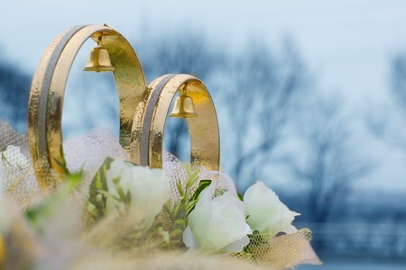 Wedding rings and flowers (decorative) on the roof of the car. Rings in the raindrops. photo