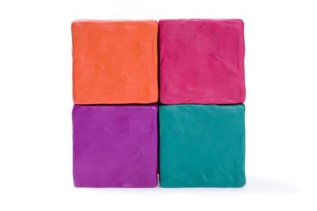 Four cubes of colored plasticine. photo