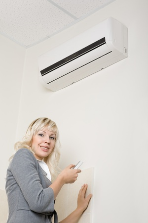 cold air: Attractive girl includes air conditionier in the office.