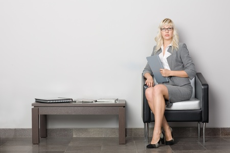 Attractive young business woman sitting in a chair. Waiting room. Stock Photo - 10309397