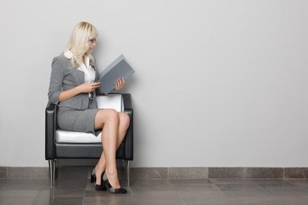 ülő: Vonzó fiatal üzletasszony ül egy széken. Váróban.