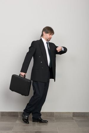 late: Businessman in a hurry, and looks at his wristwatch. Stock Photo