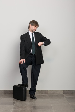 Waiting businessman looking at wristwatch. Stock Photo - 10309388