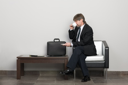 Businessman in the waiting room drinking coffee. Stock Photo - 10309396