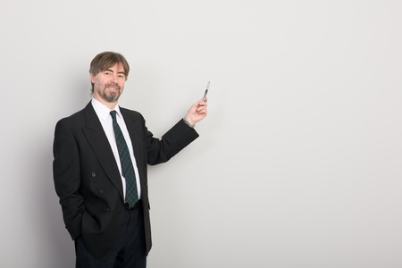 Businessman showing something on a gray background. Stock Photo - 10309473