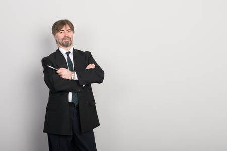 Businessman showing something on a gray background. photo