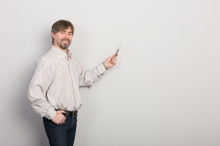 Businessman showing something on a gray background. Stock Photo - 10309384