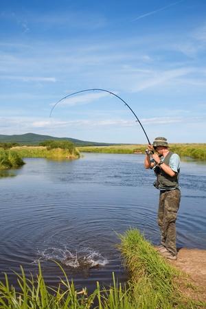hombre pescando: Pescador capturas de salm�n (salm�n rosado) en la desembocadura del r�o.  Foto de archivo