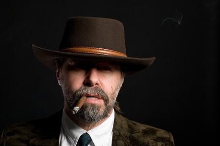 hombre fumando puro: Hombre de avanzada edad medio elegante con un cigarro. Foto de archivo
