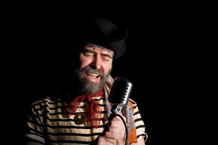 sailor man: Singer dressed as sea pirate sings in an old microphone. Stock Photo