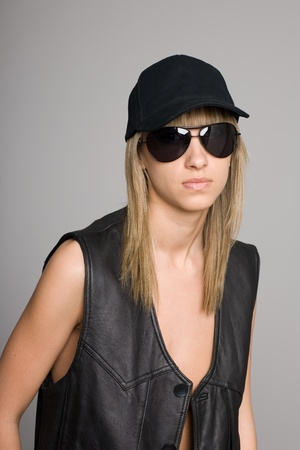 Stylish attractive blonde girl in a sunglasses and baseball cap. photo