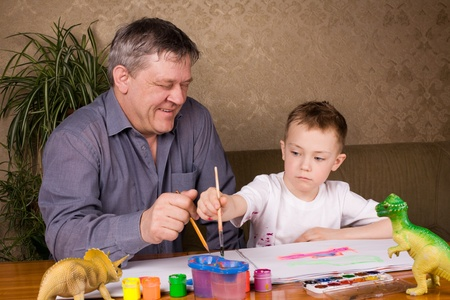 His grandfather teaches his grandson drawing paint. photo