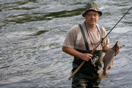 Fisherman caught a salmon (pink salmon) on the River. Early Morning. Stock Photo - 10328900