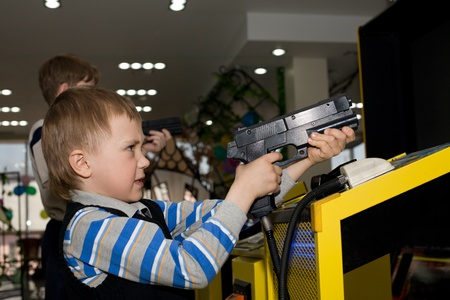Boy in the childrens amusement arcade. Playing a video game. photo
