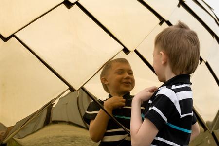 spiegelbeeld: Lachende jongetje kijkt in de spiegel. Stockfoto