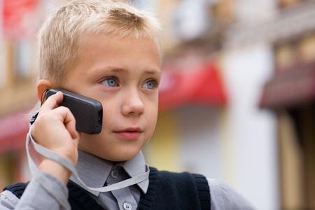 niños platicando: Little boy hablando por un teléfono celular en la calle. Foto de archivo