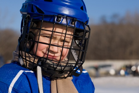 A boy plays hockey on the outdoor ice area. Boy seven years. photo