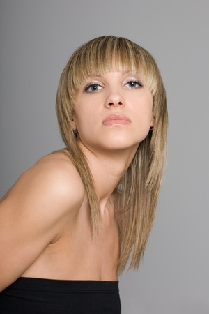 Beautiful  blonde girl with a fashionable hairdo on the gray background. photo
