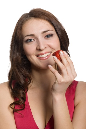 Beautiful young woman eating a fresh red stravberry. photo