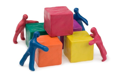 team building: Business teamwork - collective problem solving. Plasticine. Isolated. Stock Photo