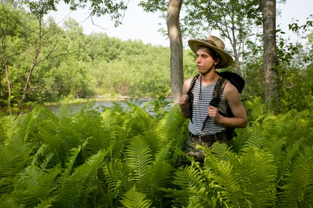 A hiker in the woods among the thickets of the fern. photo