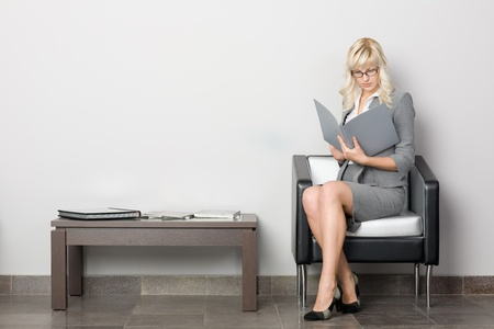 fale: Attractive young business woman sitting in a chair. Waiting room.