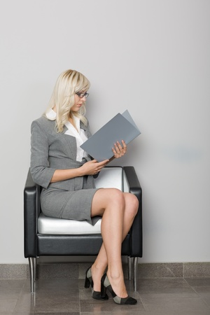 Attractive young business woman sitting in a chair. Waiting room. photo