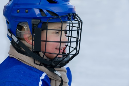 recreational sports: A boy plays hockey on the outdoor ice area. Boy seven years.