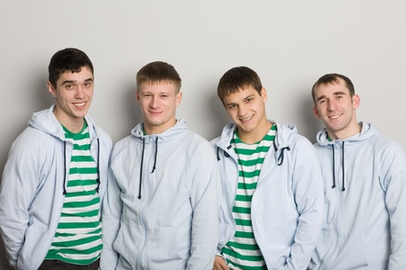 Four friends smiling against gray wall. photo