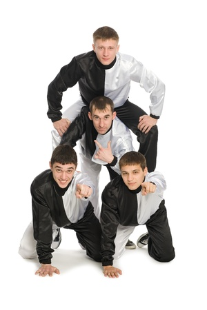 Portrait of a team of young break dancers with elements of dance in stylish uniforms. Two guys show the index finger at the camera. photo