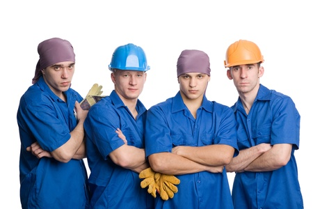 Friendly young team of construction workers. Isolated on white.