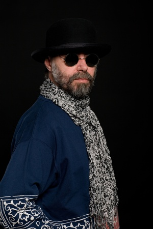 Bearded middle aged man in a bowler hat on a dark background photo