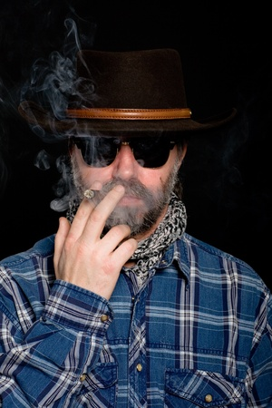 Middle aged man in a cowboy hat smoking a cigar. photo