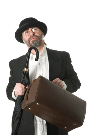 bowler hat: Traveling middle aged businessman in a business suit and an umbrella and travelling bag in his hands. Stock Photo